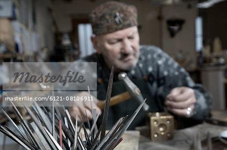 Senior male goldsmith metalworking at workshop, Bavaria, Germany