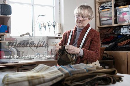 Senior female fashion designer stitching cap in workshop, Bavaria, Germany