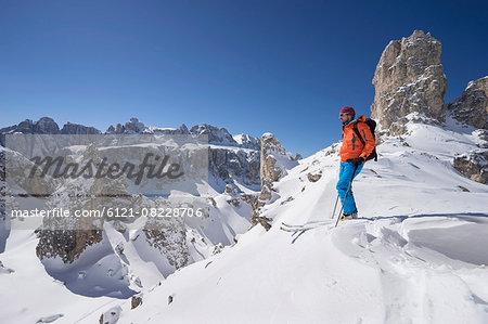 Ski tourer looking at mountains view, Val Gardena, Trentino-Alto Adige, Italy