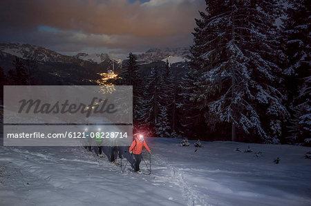 Ski mountaineers climbing on snowy mountain with head torches, Val Gardena, Trentino-Alto Adige, Italy
