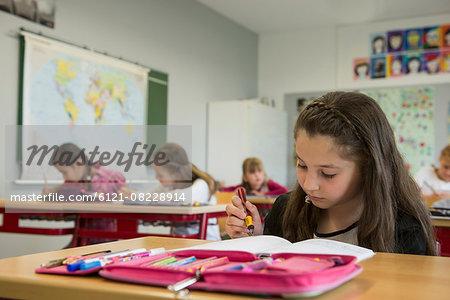 Schoolgirls writing notebooks in classroom, Munich, Bavaria, Germany