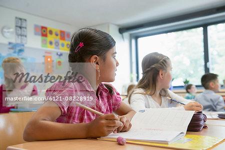 School students writing notebooks in classroom, Munich, Bavaria, Germany