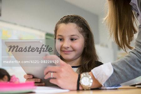 Female teacher showing a schoolgirl something on digital tablet pc in classroom, Munich, Bavaria, Germany