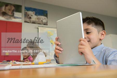 Schoolboy using a digital tablet in classroom, Munich, Bavaria, Germany