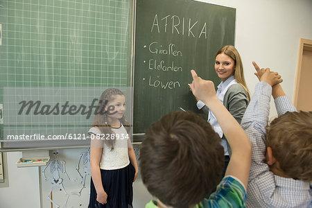 Female teacher teaching students in classroom, Munich, Bavaria, Germany