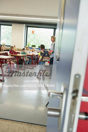 Female teacher introducing a new classmate in classroom, Munich, Bavaria, Germany