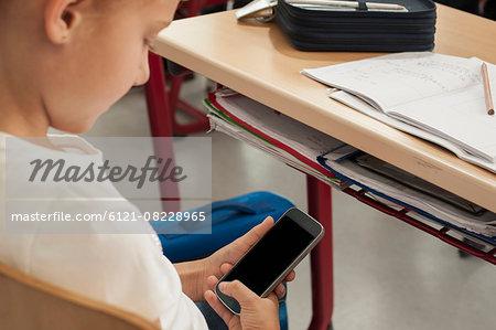 Schoolgirl using a smart phone in classroom, Munich, Bavaria, Germany