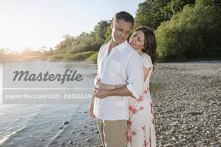 Mature couple romancing at lakeside and smiling, Bavaria, Germany
