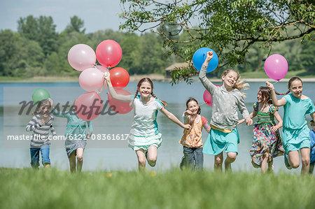 Children running in park with balloons, Munich, Bavaria, Germany