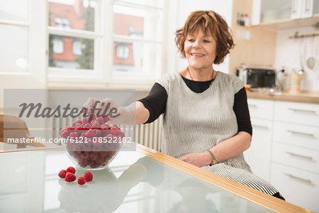 Senior woman nibbling raspberries in the kitchen, Munich, Bavaria, Germany