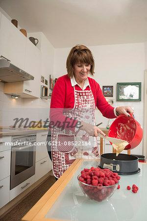 Senior woman pouring dough into a spring form pan, Munich, Bavaria, Germany