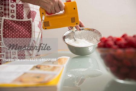Senior woman mixing meringue in mixing bowl in kitchen, Munich, Bavaria, Germany