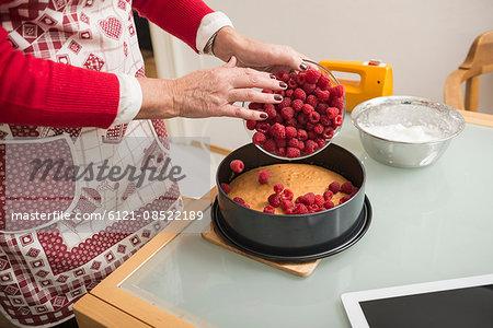 Senior woman spreading raspberries on cake base in spring form pan, Munich, Bavaria, Germany