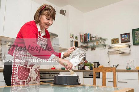 Senior woman pouring meringue on cake base in springform pan, Munich, Bavaria, Germany