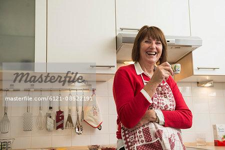 Happy senior woman wearing apron and drinking espresso coffee in kitchen, Munich, Bavaria, Germany
