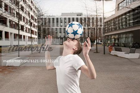 Teenage boy playing football by balancing a ball on his forehead, Bavaria, Germany