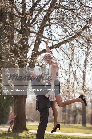 Groom lifting up bride in garden, Munich, Bavaria, Germany