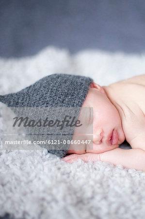 Close-up of cute newborn baby girl sleeping on rug, Fürstenfeldbruck, Bavaria, Germany