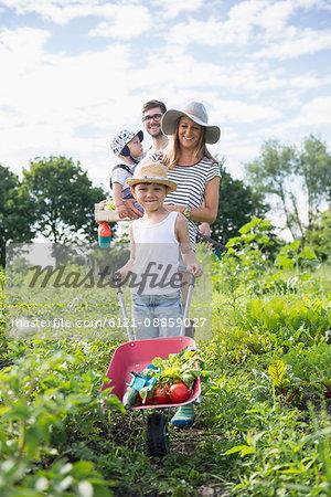 Family walking with wheelbarrow in community garden, Bavaria, Germany