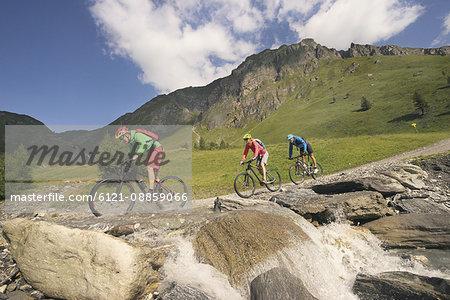 Three mountain bikers crossing stream on mountain, Zillertal, Tyrol, Austria