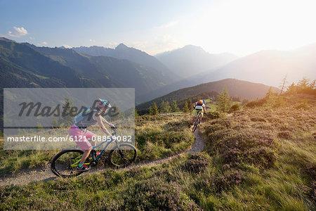 Two mountain bikers riding on hill in alpine landscape, Zillertal, Tyrol, Austria
