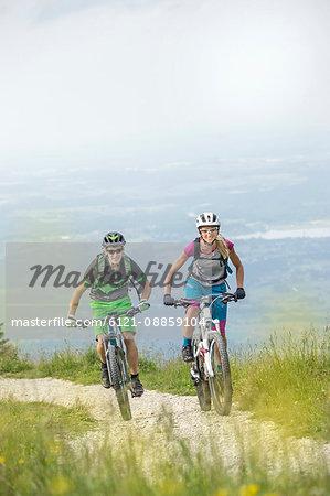 Mountain bikers cycling uphill in nature, Kampenwand, Bavaria, Germany