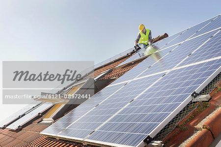 Engineer on roof installing solar panels