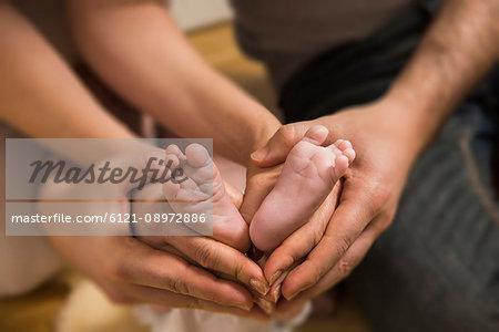 Close - up parents making heart shape symbol around baby boys feet