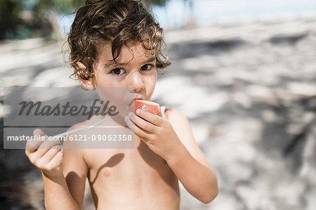 Portrait of little boy eating passion fruit