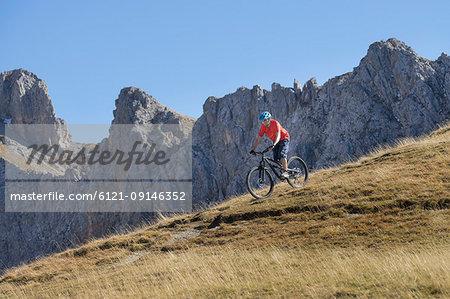 Mountain biker riding down hill in alpine landscape, Tyrol, Austria