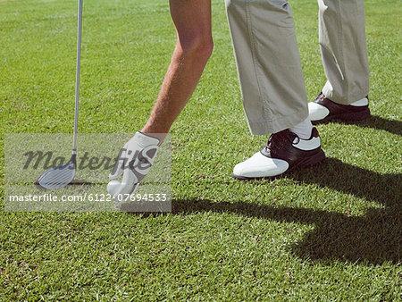 Man playing golf, picking up ball