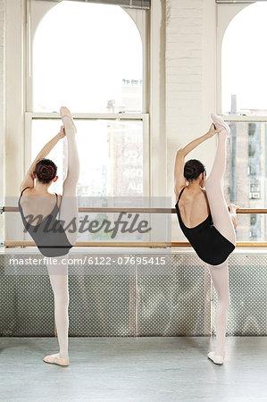 Rear view of ballerinas raising legs