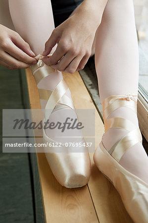 Girl tying ballet shoes