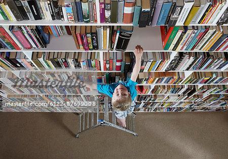 Boy using stepladder on bookshelves