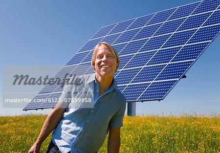Man standing in field by solar panel