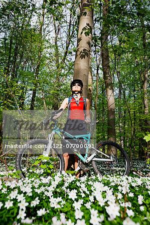 Mountain biker standing in forest