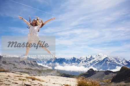 Girl jumping in rocky landscape