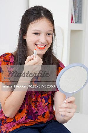 Smiling girl applying lipstick in mirror