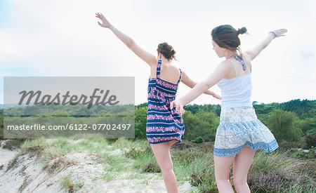 Women playing airplane on beach