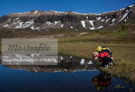 Hiker admiring reflection in still pond
