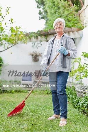 Older woman raking in backyard