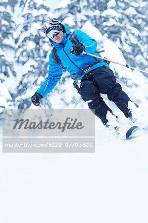 Skier coasting down snowy slope