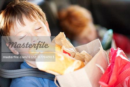 Boy with bag sleeping in backseat