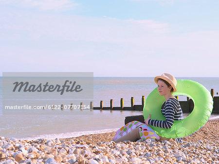 Teenage girl with ring on rocky beach