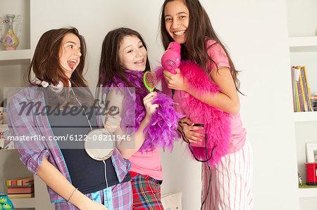 teenage girls singing , wearing pajamas