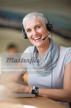 Older woman in headset using laptop