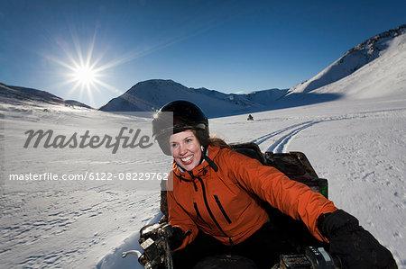 Woman driving snowmobile in snowy field