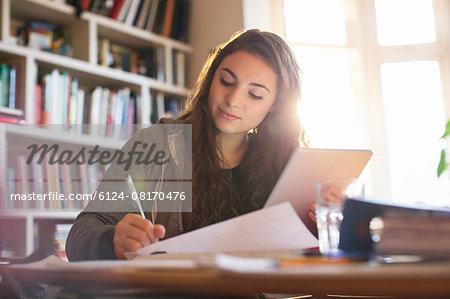 Teenage girl with digital tablet doing homework at desk