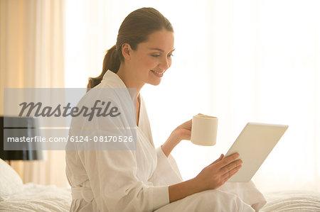Woman in bathrobe drinking coffee and using digital tablet in bedroom