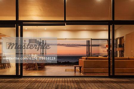 Illuminated home showcase interior overlooking ocean at sunset